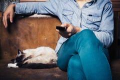 Ung man med hållande ögonen på tv för katt Royaltyfria Bilder