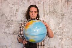 Ung man med jordklotet arkivbild