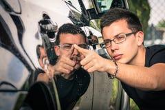Ung man med kontroll av en lyxig bil på den begagnade försäljningen Royaltyfri Fotografi