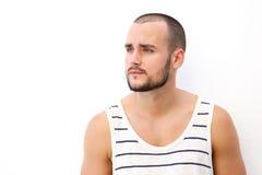 Ung man med kort hår och skägg som bort ser Royaltyfri Fotografi