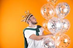 Ung man med krona- och luftballonger royaltyfria foton