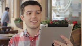 Ung man med leende under den videopd appellen på minnestavlan stock video
