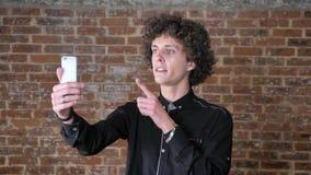 Ung man med lockigt hår som har video pratstund till och med hans telefon som ler, bakgrund för tegelstenvägg lager videofilmer