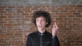 Ung man med lockigt hår som kommer upp med idé eller lösningen, pekar upp fingret och ler, lyckligt uttryck, tegelstenvägg stock video