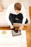 Ung man med minnestavlan på soffan Royaltyfria Bilder