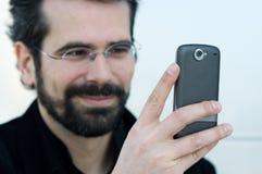 Ung man med mobiltelefonen Royaltyfria Bilder