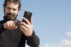 Ung man med mobiltelefonen Arkivfoton