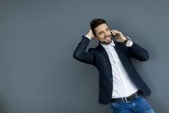 Ung man med mobiltelefonen i kontoret Fotografering för Bildbyråer