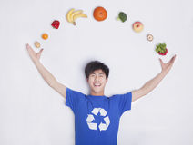 Ung man med nya frukt och grönsaker, kurva, studioskott royaltyfri bild
