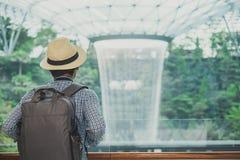 Ung man med p?sen och hatten, asiatiskt handelsresandeanseende och se till h?rlig regnvirvel p? den juvelChangi flygplatsen, gr?n arkivfoton