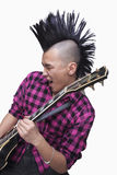 Ung man med punkrockMohawk som spelar gitarren Arkivfoton