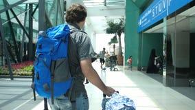 Ung man med ryggsäcken som drar resväskan i modern flygplatsterminal Resa den stiliga grabben som bort går med hans arkivfoto