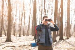 Ung man med ryggsäcken som ser kikaren som fotvandrar i skogen royaltyfria bilder