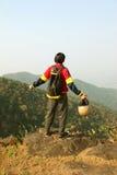Ung man med ryggsäck- och hjälmanseende med lyftta händer överst av ett berg och att tycka om dalsikt Royaltyfri Fotografi
