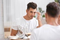 Ung man med skäggstubb som är klar för att raka nära spegeln royaltyfri foto