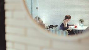 Ung man med smartphonesammanträde i kafé i spegel stock video