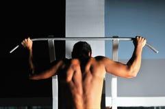 Ung man med starka armar som ut fungerar i idrottshall Fotografering för Bildbyråer