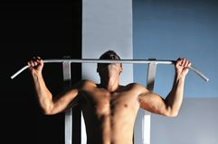 Ung man med starka armar som ut fungerar i idrottshall Arkivbild