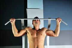 Ung man med starka armar som ut fungerar i idrottshall Arkivfoton