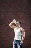 Ung man med starka muskler, vattendrink, når utbildning Royaltyfri Fotografi
