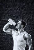 Ung man med starka muskler, vattendrink, når utbildning Royaltyfria Foton