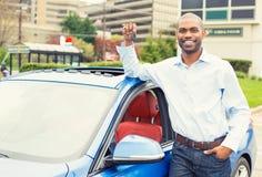 Ung man med tangenterna som står med hans nya bil Arkivfoto