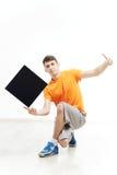 Ung man med tecknet som han rymmer mot en vit bakgrund arkivbilder