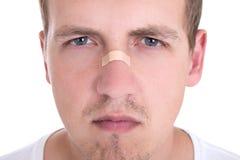 Ung man med tejpen över hans näsa royaltyfri fotografi