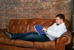 Ung man med tidskriften på soffan Royaltyfri Bild