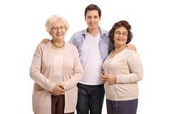 Ung man med två äldre kvinnor Arkivbild