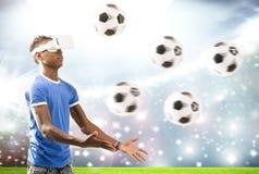 Ung man med virtuell verklighethörlurar med mikrofon eller exponeringsglas 3d över fotbollfält på stadionbakgrund Royaltyfria Foton