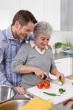 Ung man och äldre kvinna som tillsammans lagar mat i köket arkivfoton