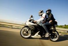 Ung man och en kvinna på en motorcykel Arkivbild