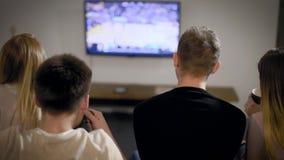 Ung man och hållande ögonen på TV för kvinna