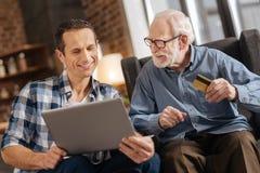 Ung man och hans äldre fader som gör online-shoppa tillsammans royaltyfri bild