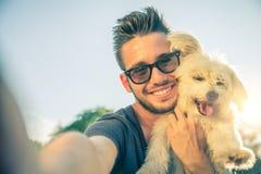 Ung man och hans hund som tar en selfie