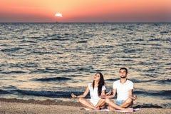 Ung man och kvinna att göra yoga och meditera på stranden på gryning sund livsstil för begrepp royaltyfria bilder