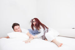 Ung man och kvinna, i att le för kuddekamp Royaltyfri Fotografi
