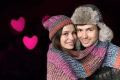 Ung man och kvinna i hans armar på bakgrunden av hjärtor man för begreppskyssförälskelse till kvinnan Royaltyfria Bilder