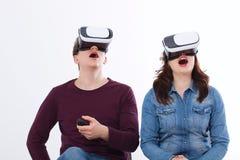 Ung man och kvinna i tillfällig kläder i faktisk skyddsglasögon, vr som isoleras på vit bakgrund teknologi- och innovationbegrepp fotografering för bildbyråer