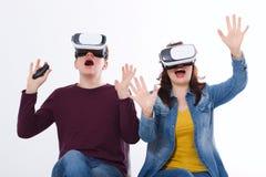 Ung man och kvinna i tillfällig kläder i faktisk skyddsglasögon, vr som isoleras på vit bakgrund teknologi- och innovationbegrepp arkivfoto