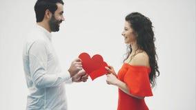 Ung man och kvinna med armar runt om de som rymmer valentinhjärtor, medan le för kameran Isolerat på stock video