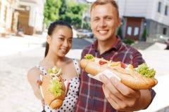 Ung man och kvinna med hotdogs på gatan Arkivfoto