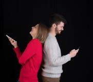 Ung man och kvinna med mobiltelefoner Arkivfoto