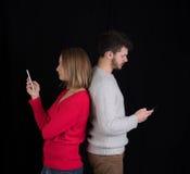 Ung man och kvinna med mobiltelefoner Fotografering för Bildbyråer