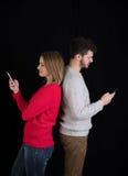Ung man och kvinna med mobiltelefoner Royaltyfri Fotografi