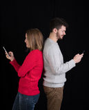 Ung man och kvinna med mobiltelefoner Royaltyfria Bilder