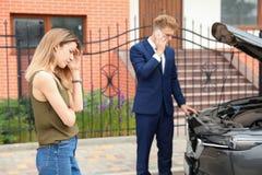 Ung man och kvinna nära den brutna bilen arkivfoto