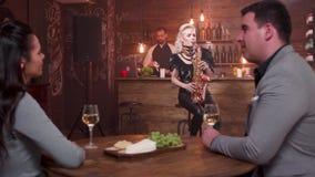 Ung man och kvinna på ett datum som lyssnar till en levande kapacitet på en saxofon arkivfilmer
