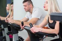 Ung man och kvinna som cyklar i idrottshallen som övar ben som gör den cardio genomköraren som cyklar cyklar Arkivfoto